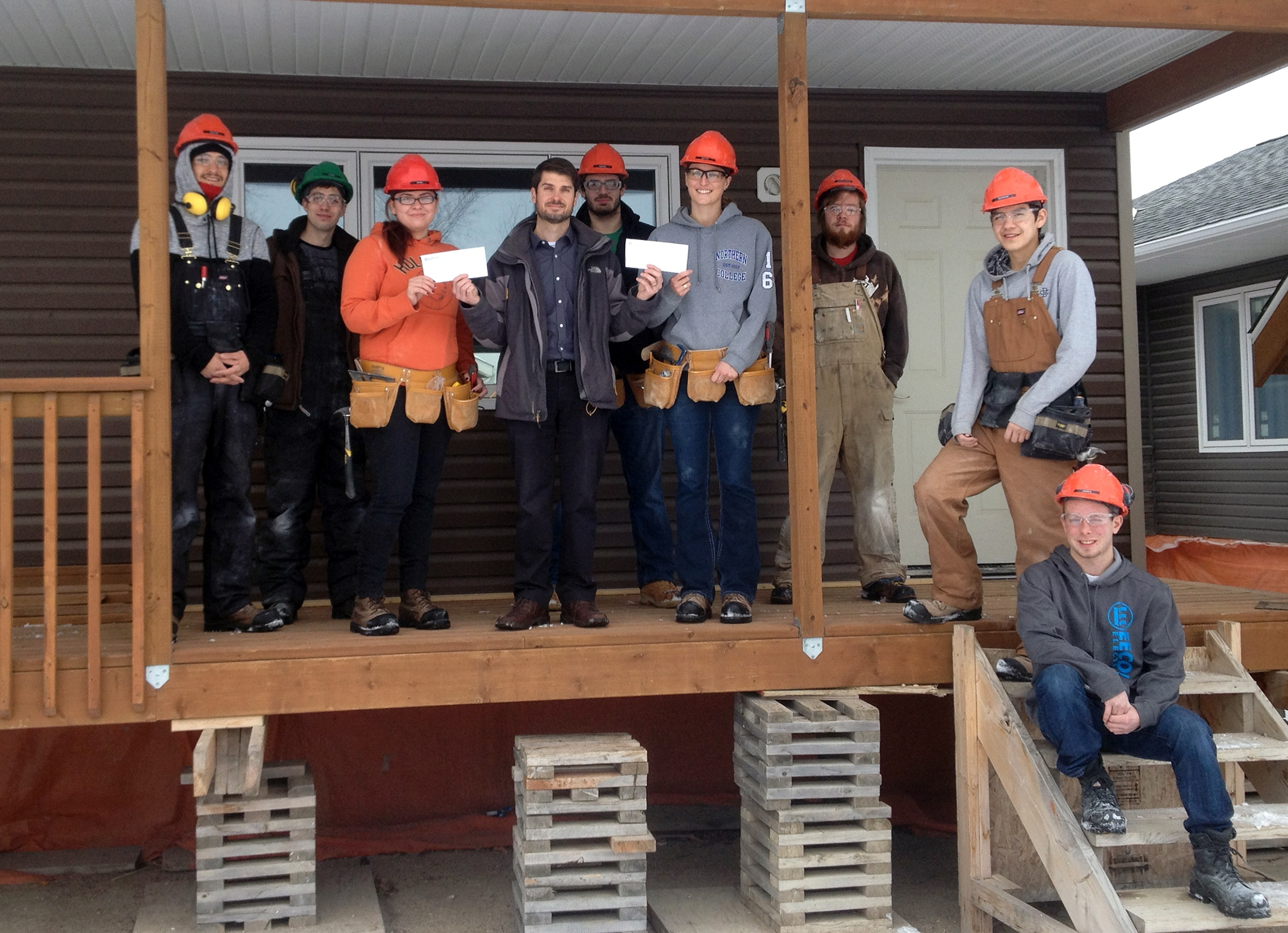 Photo (of Dauphin Co-op building division manager Steve Bunka presenting Nikki Welburn (left) and Kathy Gale (right) with awards, with the rest of the carpentry students outside the home they're building) provided by ACC